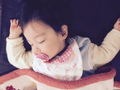 おしゃぶりをくわえて寝る赤ちゃん